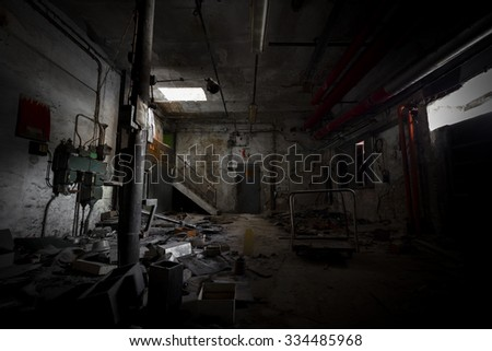 garbage, dirty room in an abandoned old factory, poor light - stock photo