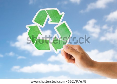 garbage disposal, environment and ecology concept - close up of hand holding green recycling sign over blue sky and clouds background