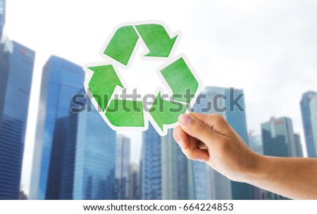 garbage disposal, environment and ecology concept - close up of hand holding green recycling sign over city skyscrapers background