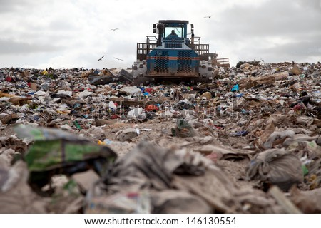 Garbage piles up in landfill site each day while truck covers it with sand for sanitary purpose - stock photo