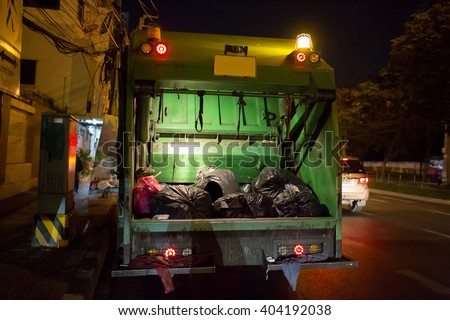 Garbage Truck On A Night Shift - stock photo
