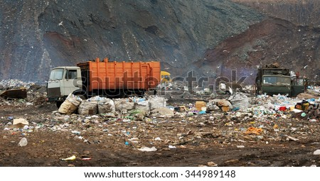 Garbage truck unloading at the dump - stock photo