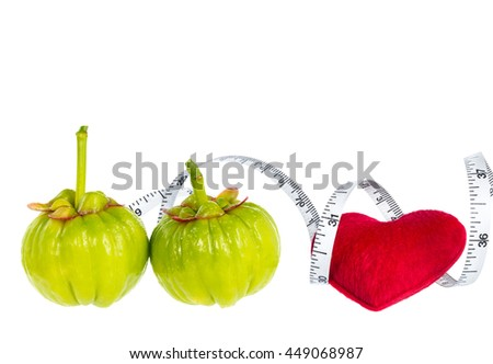 Garcinia cambogia fresh fruit with red heart and measuring tape, isolated on white. Garcinia is spice plants. It helps in the metabolism contain high vitamin C and hydroxy citric acids for weight loss