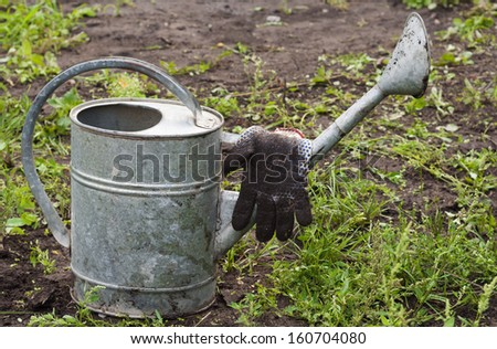 Garden accessories - a watering can and gloves - stock photo