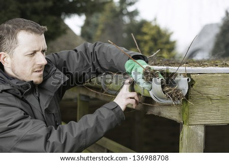 garden and house work. janitor cleaning a roof gutter. - stock photo