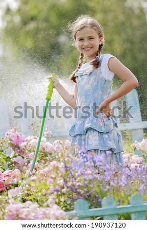 Garden and summer fun - beautiful girl watering roses with garden hose in the garden - stock photo