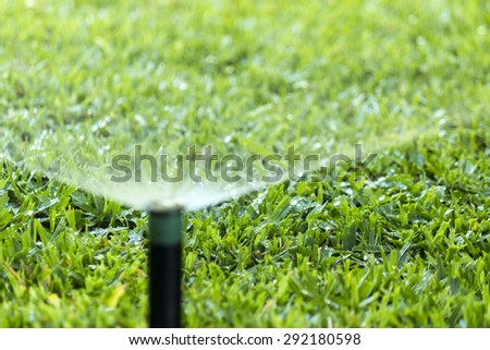 Garden automatic Irrigation system spray watering lawn. - stock photo