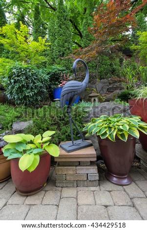 Garden Backyard Japanese Asian Theme Design Landscaping with Plants Crane Sculpture and Stone Lantern - stock photo
