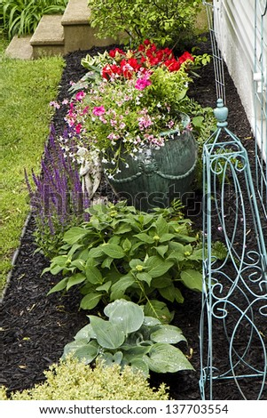 Garden bed with flowers, hostas, boxwood and rhodendrons - stock photo