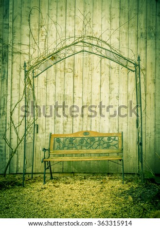 Garden bench Idyllic image with a garden bench under a metal arbor, near the wooden wall of a barn, in a german residence backyard. - stock photo