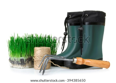garden boots and tools with sprouts seeds on a white isolated background