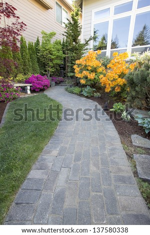 Garden Brick Paver Path Walkway with Green Grass Lawn and Landscaping Plants
