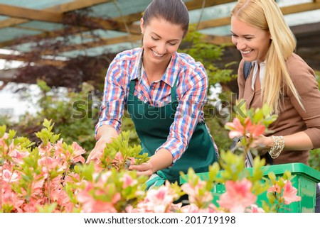 Garden center woman show flowers to smiling customer buying plants - stock photo