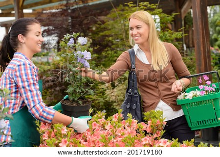 Garden center worker selling potted flower to customer buying plants - stock photo