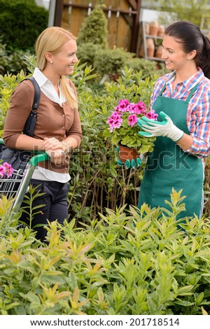 Garden center worker selling potted flower to customer woman shopping - stock photo