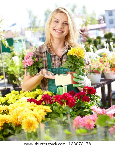 Garden center worker smiling and holding up yellow flower - stock photo