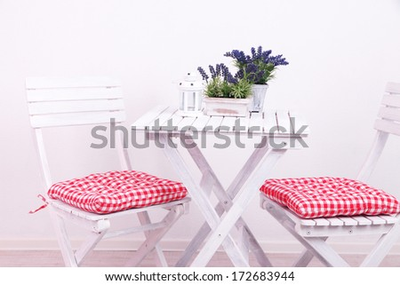 Garden chairs and table with flowers on white background - stock photo