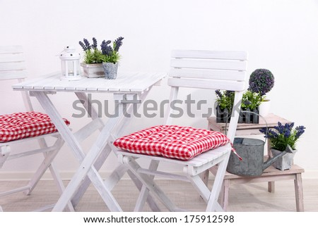 Garden chairs and table with flowers on wooden stand on white background