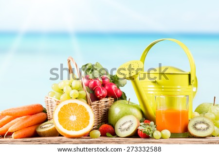 Garden concept, fresh fruits, carrot juice and vegetables on wooden table, watering can, seeds, plants - stock photo