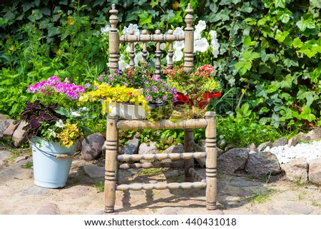 Garden decoration with a old chair and  plants makes a unique eyecatcher for rustic garden stye. - stock photo