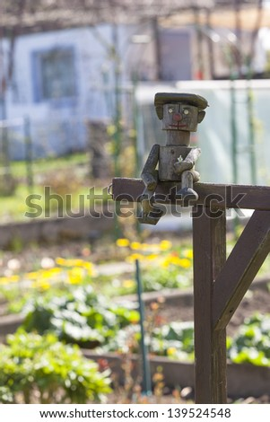garden decoration, wooden puppet sitting on entrance.