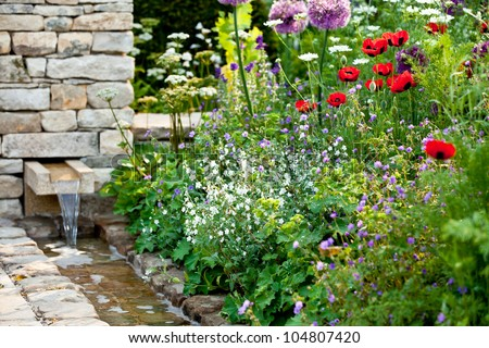 Garden flowers with stone walled stream - stock photo