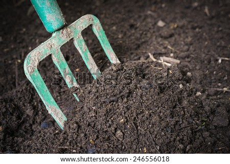 Garden fork turning  black composted soil in compost bin ready for gardening, close up. - stock photo