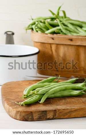 Garden fresh green beans (string beans) on a wood cutting board are ready to be prepared for a meal.  A produce basket full of beans sits in the background with a white and black enamel pot.
