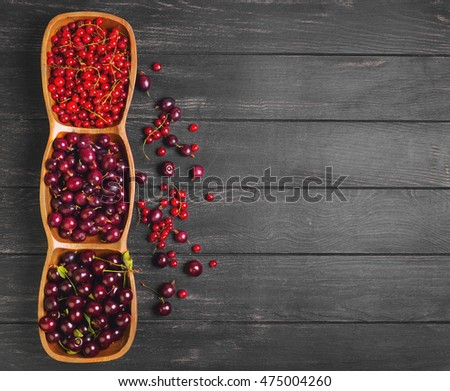 Garden fresh red berry fruit. Gooseberry, cherry, red currant. Red berries are scattered on dark wooden background black gooseberry, cherry, red currant. Top view.