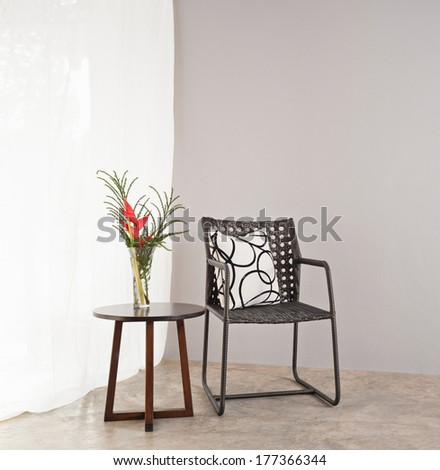 Garden furniture chair in simple setting and side table  - stock photo
