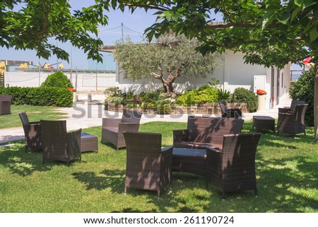 Garden furniture on lawn in courtyard a hotel spa - stock photo