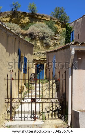 garden gate between typical houses with blue shutters in the small mountain village of Cadenet, Provence, south France, Luberon Massif - stock photo