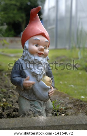 garden gnome in flowerbed - stock photo