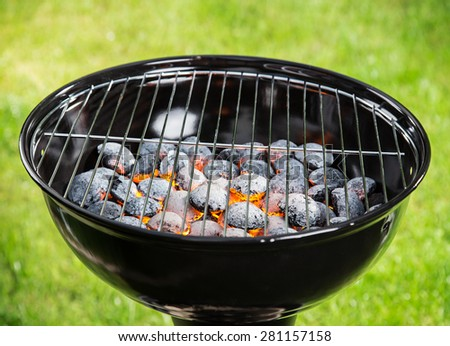 Garden grill with blistering briquettes, close-up. - stock photo