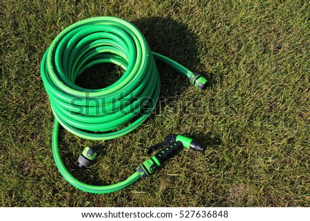 Garden hose bundle with a spray and connectors on the mown lawn in the summer garden