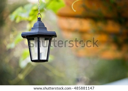 Garden lantern upon green lawn. Outdoor decoration and lighting.