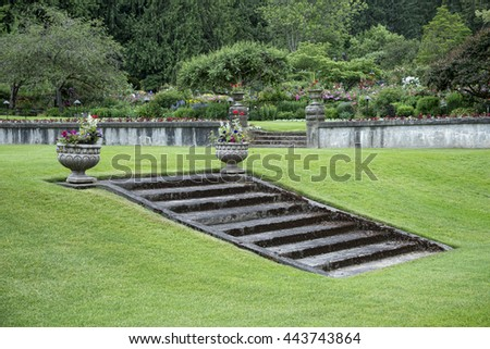 Garden lawn with built in stairway, potted plants, and stone fence - stock photo