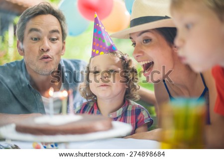garden party for the little girl's birthday, the whole family helping her to blow out the candles, the garden is decorated with balloons and colors are bright - stock photo