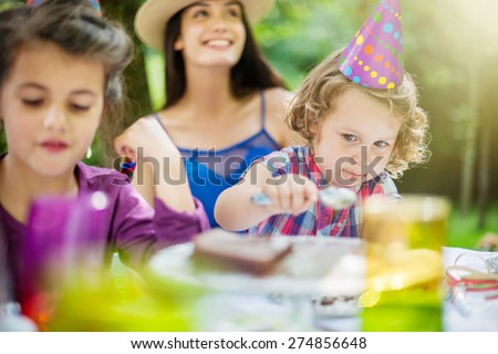 Garden party, greedy little girl eating chocolate birthday cake in family - stock photo