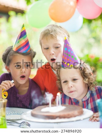 garden party with family for little girl's birthday, children blowing out the candles on the cake, the garden is decorated with balloons and colors are bright