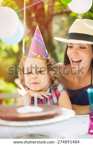 garden party with family for little girl's birthday, children blows out the candles on the cake, the garden is decorated with balloons and colors are bright