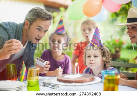 garden party with family for little girl's birthday, Dad lights the candles on the cake , the garden is decorated with balloons and colors are bright - stock photo