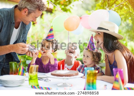 garden party with family for little girl's birthday, Dad tries to light the candles on the cake , the garden is decorated with balloons and colors are bright - stock photo