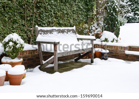 Garden patio bench with snow - stock photo