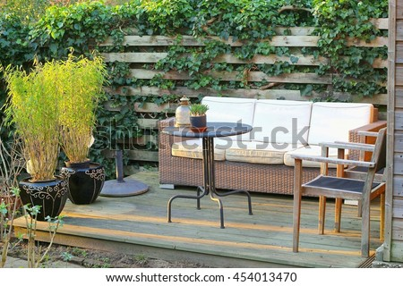 Garden patio with sofa, wooden floor and bamboo plants, Netherlands
