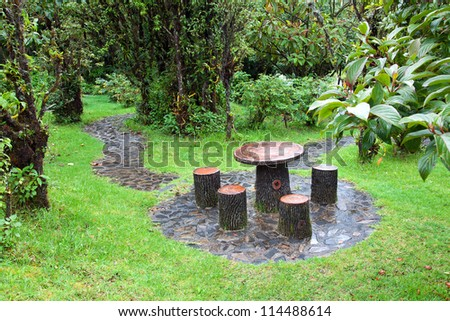Garden patio with table and chairs after raining. - stock photo
