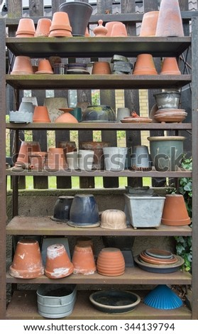 Garden pots in various shapes and form in a wooden rack outdoors.