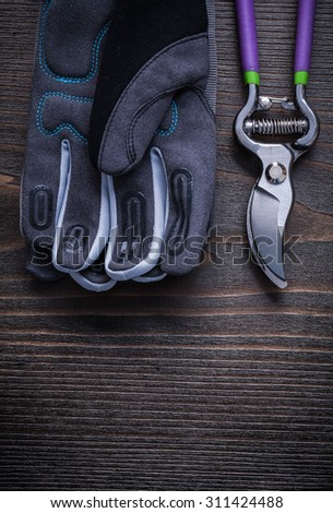 Garden pruner gardening gloves on vintage wood board agriculture concept. - stock photo
