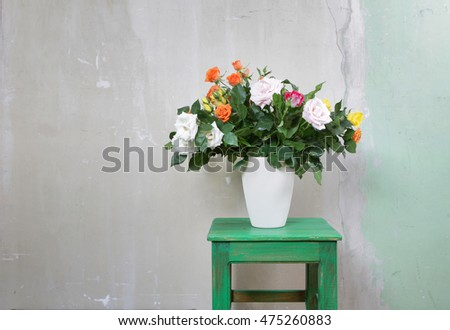 garden roses in a vase on a wooden rustic stool