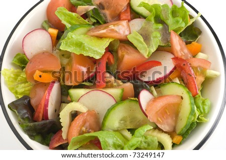 Garden salad with balsamic vinaigrette dressing isolated on white background